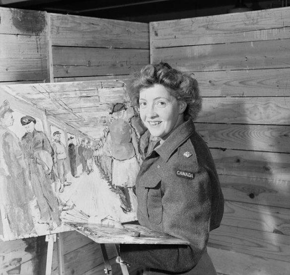 Photographie en noir et blanc de Molly Lamb Bobak qui prend la pose devant un chevalet, des brosses et une palette en main. Mme Bobak porte une veste-blouson de l'armée et elle sourit à la caméra. La peinture inachevée derrière elle représente des membres féminins et masculins de l'Armée canadienne, debout dans une pièce.
