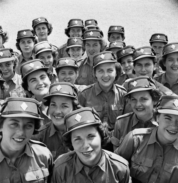 Photographie en noir et blanc d'un rassemblement de recrues souriantes du CWAC. Elles portent leur tenue de cérémonie estivale et des casquettes arborant un insigne de coiffure en forme de diamant.