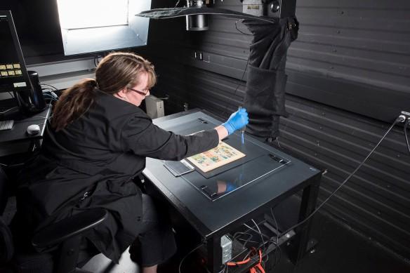 Une bande dessinée est placée sur une surface plane noire sous une feuille de plexiglas. Une femme est penchée sur la surface; elle enlève la poussière du plexiglas à l'aide d'un souffleur antistatique. La lentille d'un appareil photo est visible au-dessus de la table.