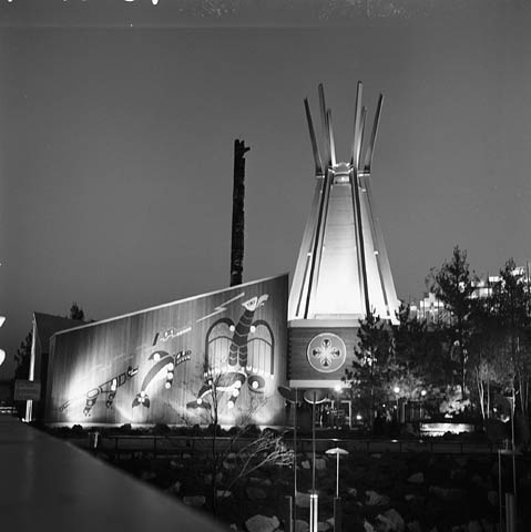 Une photographie en noir et blanc d'un édifice dont la façade est décorée de motifs d'art autochtone, contigu à une structure en forme de tipi. On aperçoit le haut d'un mât totémique derrière l'édifice.