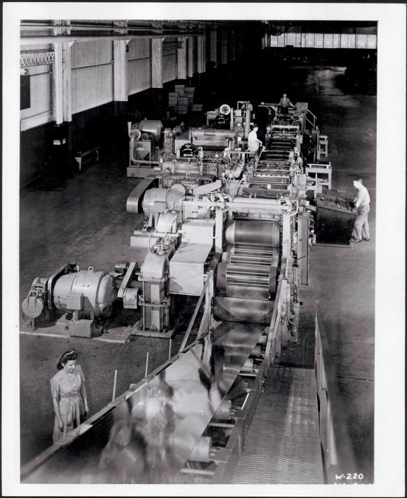 Photographie noir et blanc montrant des travailleurs manœuvrant une machine servant à rouler l'acier et à le transformer en multiples panneaux.