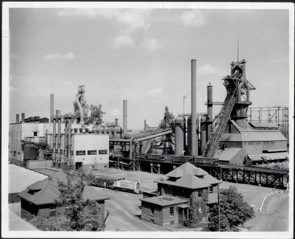Photographie noir et blanc montrant en gros plan des hauts fourneaux d'un site industriel.