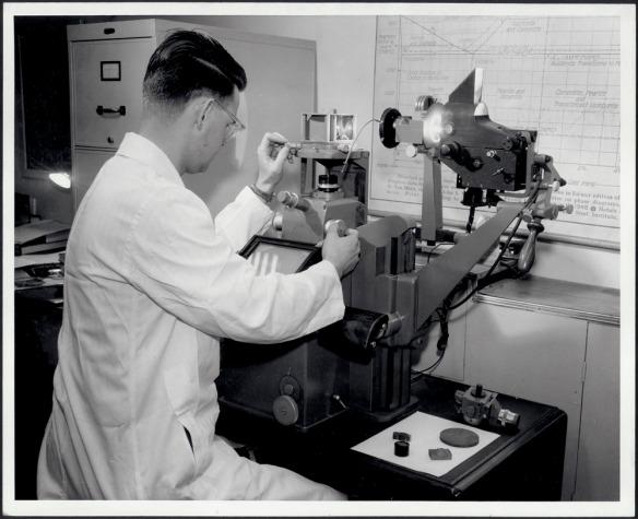 Ingénieur du laboratoire de métallurgie testant la qualité de la structure de l'acier avec un appareil appelé « photomicrographe » vers 1960 (MIKAN 4915724)