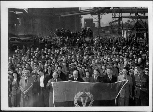 Photographie noir et blanc montrant un regroupement de personnes tenant un drapeau orné d'un « V » signifiant Victoire.