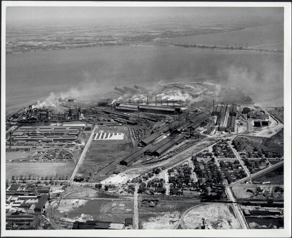 Photographie noir et blanc montrant un complexe industriel servant à la production et à la transformation de l'acier.