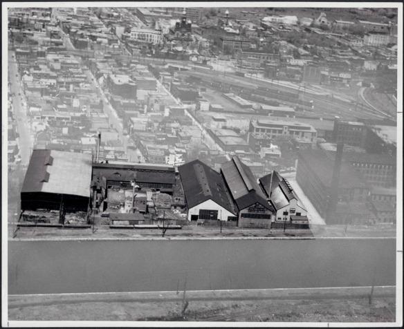Photographie noir et blanc montrant une usine aux abords d'un canal. On y aperçoit en arrière-plan d'autres usines ainsi que les voies ferrées servant au transport des matériaux d'acier.