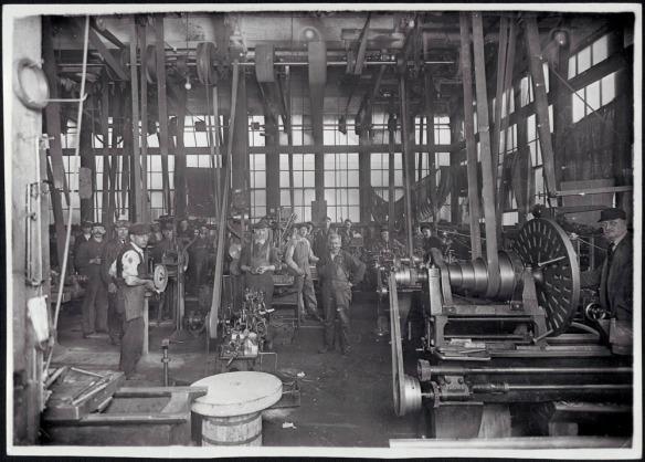 Photographie noir et blanc montrant des hommes dans une usine. On peut y apercevoir en arrière-plan un nombre important de travailleurs faisant fonctionner manuellement les premières machines mécaniques.