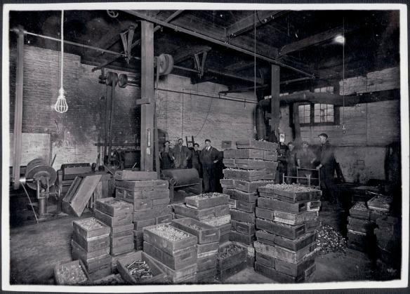 Photographie noir et blanc montrant des employés à l'intérieur d'une usine en train d'empaqueter des produits.