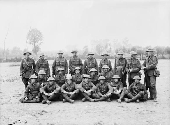 Une photographie en noir et blanc d'un groupe de soldats en uniforme dans un champ.