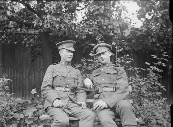 Photographie en noir et blanc de deux soldats en uniforme assis sur un banc. L'homme à droite regarde directement la caméra et arbore un sourire discret.