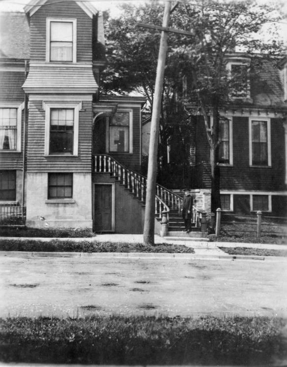 Photographie en noir et blanc d'Edward M. Saunders, debout au pied de l'escalier devant une maison de style victorien à trois étages. M. Saunders porte un complet et un chapeau noirs. La photographie a été prise de l'autre côté d'une rue résidentielle.