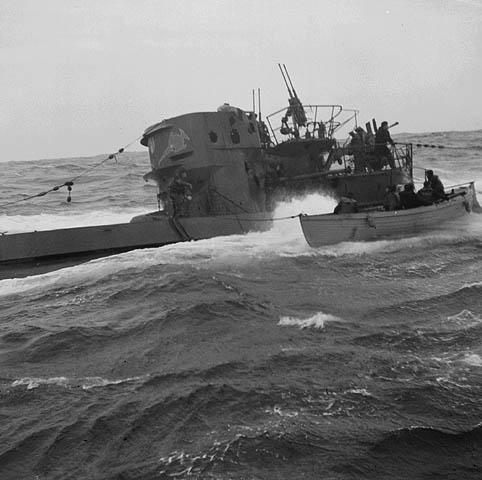 Photographie en noir et blanc montrant un sous-marin et une baleinière côte à côte. Des membres d'équipage du sous-marin se trouvent sur le pont. Les personnes à bord de la baleinière sont assises.