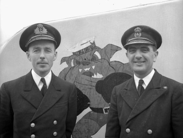 Photographie noir et blanc montrant deux hommes en uniforme de la marine posant devant la tourelle avant de leur corvette. Entre les deux hommes, une image peinte sur la tourelle représente un bulldog se tenant debout avec un chapeau de marin et des gants de boxe.