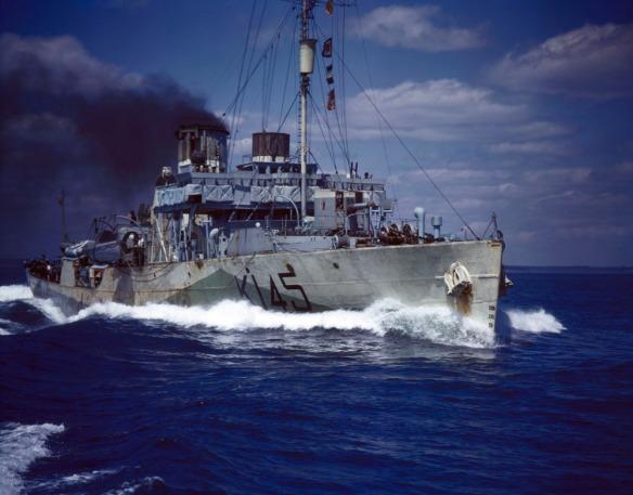 Photographie en couleurs d'une corvette de la Marine royale du Canada voguant à plein régime. Une épaisse fumée noire s'échappe d'une cheminée. Sur le bateau de couleur grise, le numéro K145 est écrit en noir.