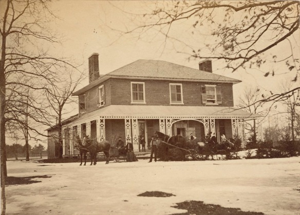 Image en noir et blanc d'une maison entourée de neige fondante. Devant la maison, il y a deux traîneaux à chevaux et des personnes autour.