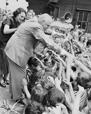 Un homme âgé, debout sur une estrade, tend la main vers un groupe d'enfants.