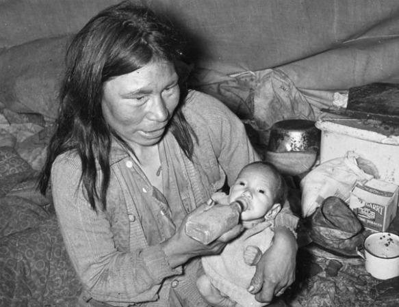Photo noir et blanc d'une femme inuite amaigrie assise dans une petite tente avec son bébé, devant des provisions. La femme nourrit son bébé à l'aide d'un biberon rectangulaire.
