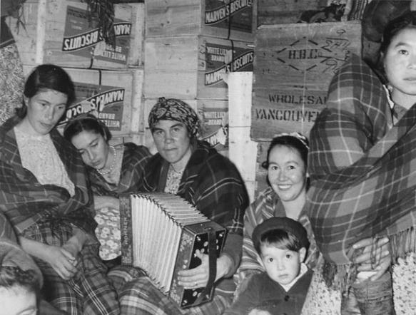 Photo noir et blanc de cinq femmes. Quatre sont assises, et une autre, à l'extrême droite, est debout avec un bébé enroulé dans un châle à carreaux. La femme au centre joue de l'accordéon, et la femme à sa gauche a un jeune garçon sur ses genoux. Des caisses de bois portant l'inscription « Marven's Biscuits » sont empilées derrière elles, et une autre caisse dit « H.B.C. Wholesale Vancouver ».