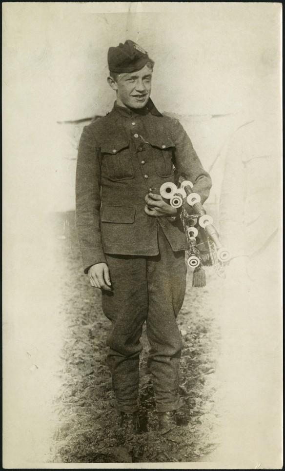 Photographie en noir et blanc d'un jeune homme vêtu d'un uniforme militaire et tenant sa cornemuse.