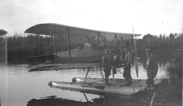 Une photographie en noir et blanc montrant un hydravion au bord d'un lac. Deux hommes se tiennent debout sur les flotteurs près de l'hélice et un troisième se tient à droite, sur la rive. Une quatrième personne, visible en partie, regarde l'avion.