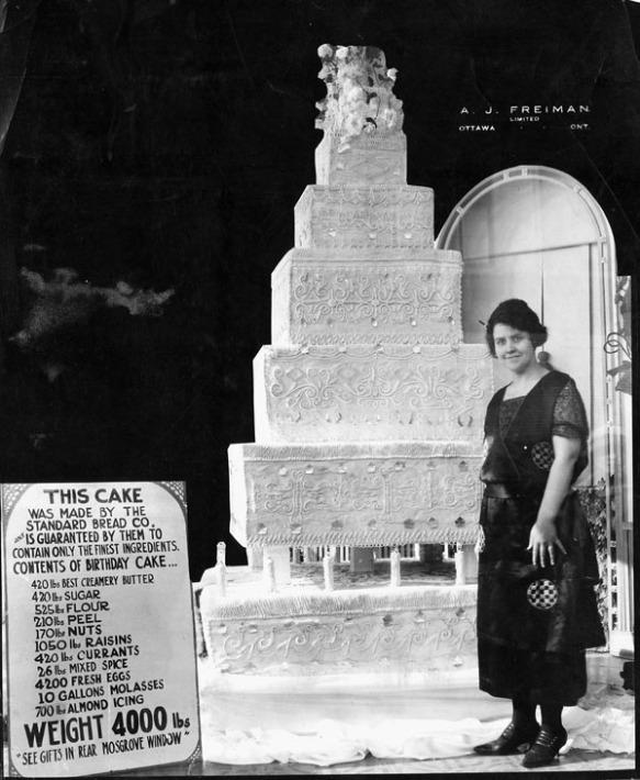 Photo noir et blanc d'un énorme gâteau avec une jeune femme debout à sa gauche. De l'autre côté, une affiche montre la liste des ingrédients.