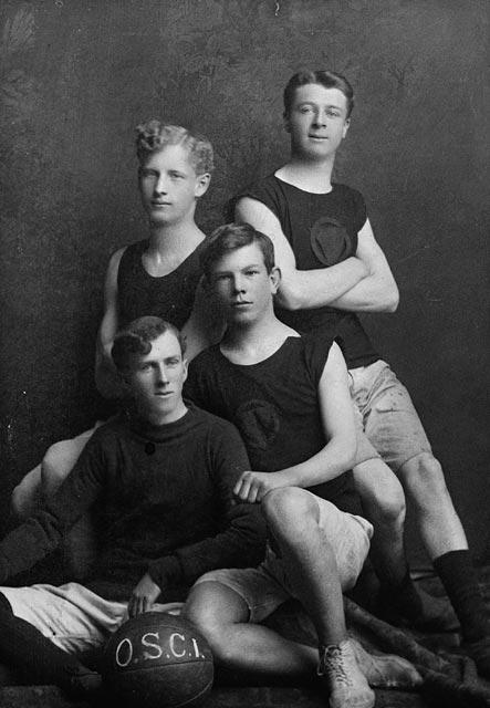 Une photographie en noir et blanc montrant quatre jeunes hommes posant autour d'un ballon de basketball.