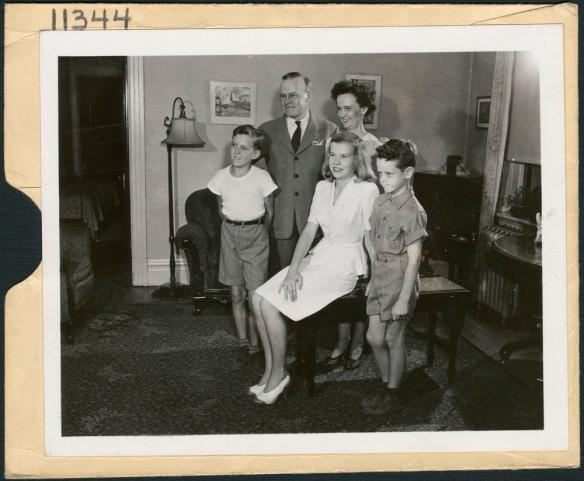 Photographie noir et blanc d'une famille comprenant une femme, un homme et trois enfants dans un salon.