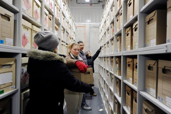 Photo couleur montrant quatre personnes debout au milieu d'une allée, entre deux rayons, plaçant des boîtes sur des étagères.