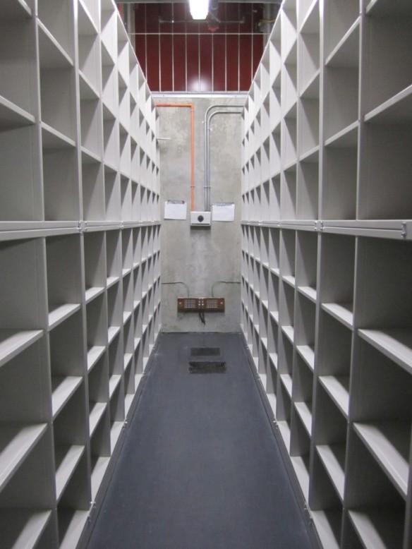 Un corridor, dans un édifice, avec des étagères blanches de chaque côté.