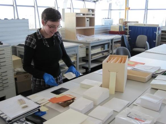 Photo couleur d'une femme portant des gants de nitrile qui retire un négatif d'une enveloppe. La table devant elle est couverte d'enveloppes et de boîtes d'archives.