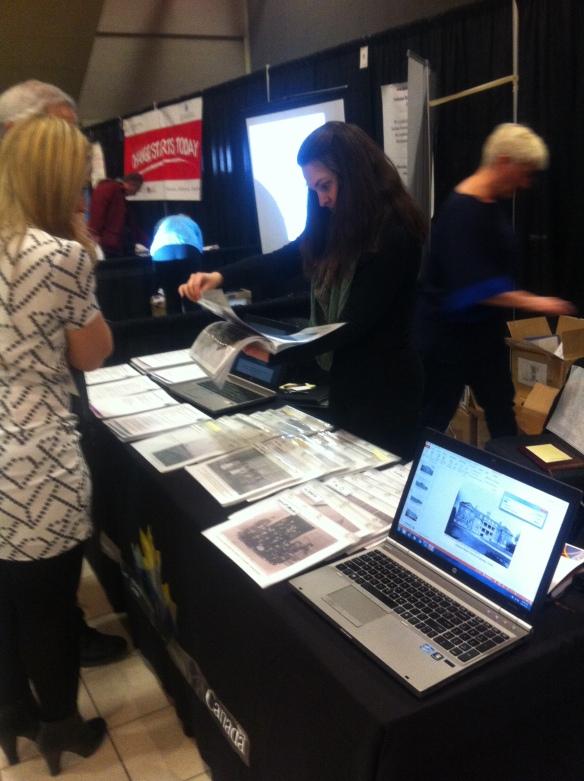 Photo d'un kiosque présentant de nombreuses photos et un ordinateur sur le bord d'une table. Une dame aux cheveux bruns qui travaille au kiosque trouve une photo pour un couple. Un autre kiosque est visible à l'arrière-plan.