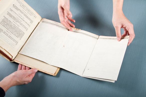 Une photo en couleur d'un livre ouvert avec une carte plié que deuux mains commencent à déplier.