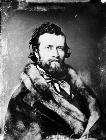 Photographie noir et blanc d'un jeune homme barbu qui regarde l'appareil photo. Il porte un manteau de fourrure et une élégante cravate.