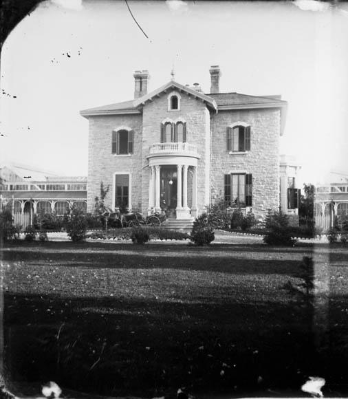 Photographie noir et blanc d'une vaste et majestueuse demeure, dont la porte centrale est flanquée de larges fenêtres. Une calèche se trouve dans l'entrée.
