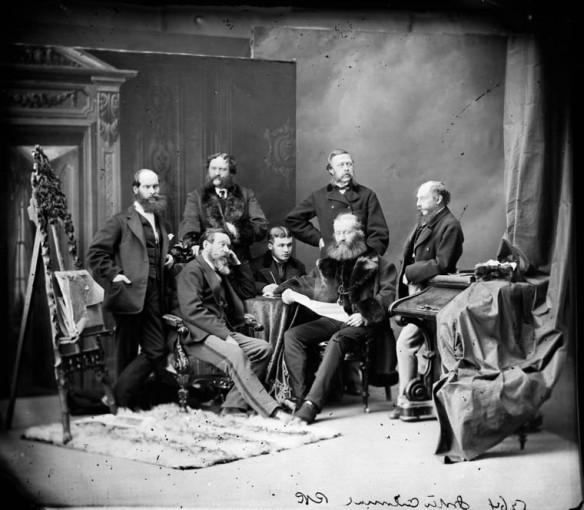 Photographie de studio noir et blanc d'un groupe d'hommes dans diverses postures, chacun regardant dans une direction différente.