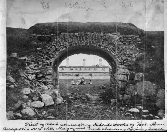 Photographie en noir et blanc d'une arche en pierre et vue par celle-ci, en arrière-plan, d'un grand immeuble clôturé avec terrain à l'avant. Une femme et cinq enfants apparaissent au centre, assis sur le sol.