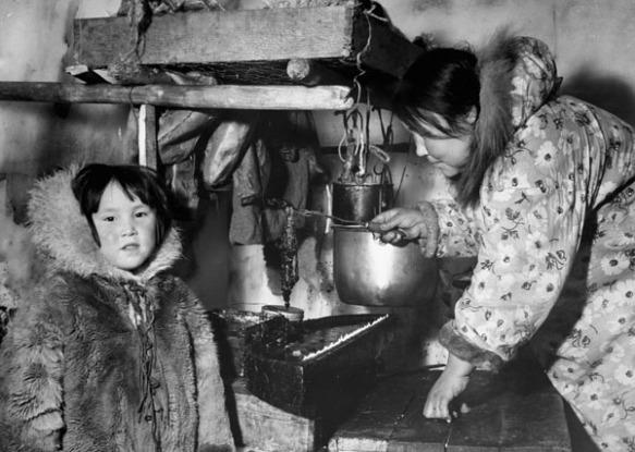 Photo noir et blanc d'une femme inuite dans un igloo qui porte une parka à motif floral et manipule une lampe à l'huile de phoque. Un jeune inuit portant une parka en fourrure se trouve près d'elle.