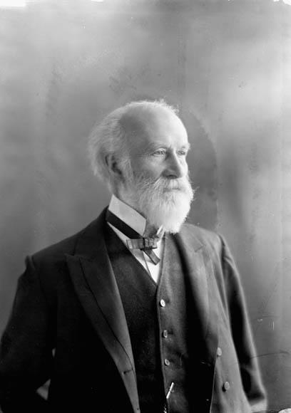 Photographie noir et blanc montrant un homme âgé portant un veston de complet, un gilet et un nœud papillon.