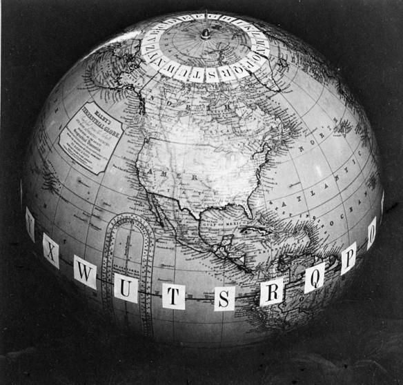 Photographie noir et blanc d'un globe terrestre montrant l'Amérique du Nord, avec des lettres fixées sur chaque méridien, tant autour du pôle Nord que de l'équateur.