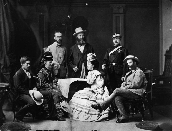 Photographie noir et blanc d'un groupe de personnes. Deux femmes sont assises, face à face. Un homme est assis à leur droite, et un autre, à leur gauche. Trois hommes se tiennent debout derrière eux.