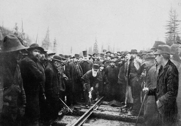 Photographie noir et blanc d'un homme martelant un rail de chemin de fer. Il est entouré d'un groupe d'hommes, dont certains fixent l'appareil photo et d'autres regardent les rails.