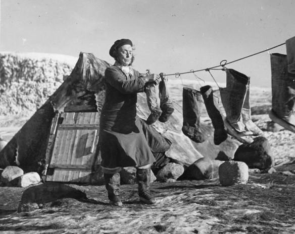 A black and white photograph of a woman standing in front of a tent and hanging seal boots on a a clothesline.