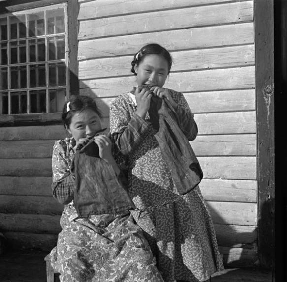 Photo noir et blanc de deux filles inuites, une debout et l'autre assise, devant une maison en bois. Elles mâchent des pièces de peau de phoque en forme de bottes.