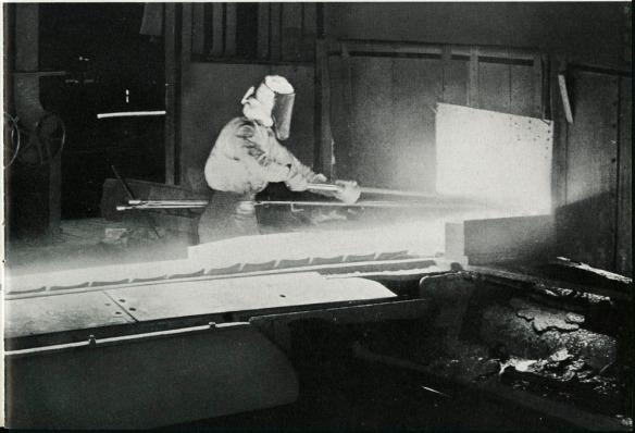 Photographie noir et blanc montrant un ouvrier manipulant une barre de fer chauffée.