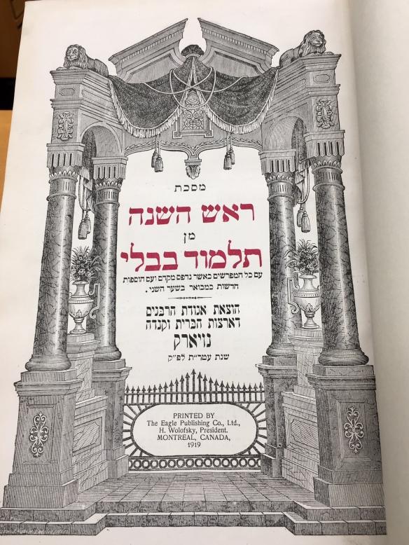 Photographie en couleur d'un livre ouvert, montrant des écrits en caractères hébraïques.