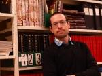 Photographie en couleur d'un homme devant une bibliothèque.