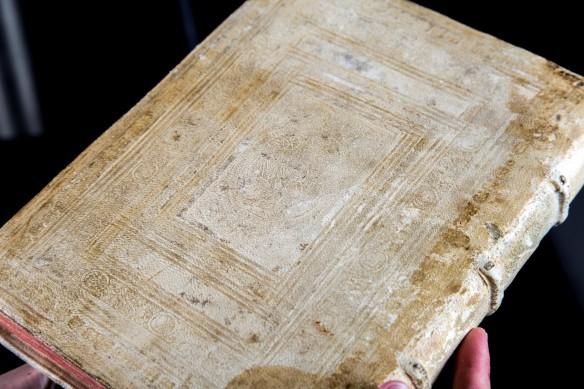 Gros plan de la couverture arrière d'un livre relié en cuir blanc taché. Le cuir est décoré de lignes et de motifs à peine visibles.