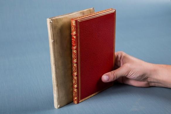 Une main tient deux livres verticalement sur fond gris-bleu. Celui de gauche a une couverture beige très simple; celui de droite a une couverture rouge et des dorures.