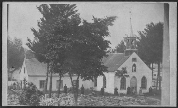 Photo en noir et blanc d'une église, derrière des arbres, près de laquelle se tiennent des fidèles.