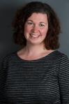 Photographie en couleur d'une femme souriante portant un gilet avec des rayures noires et grises.